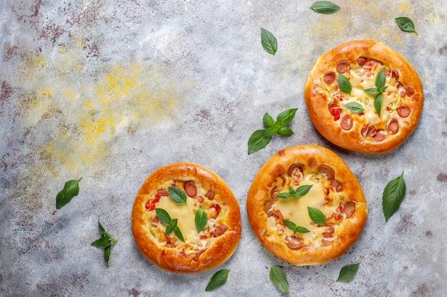 Маленькие домашние пиццы свежие с базиликом.