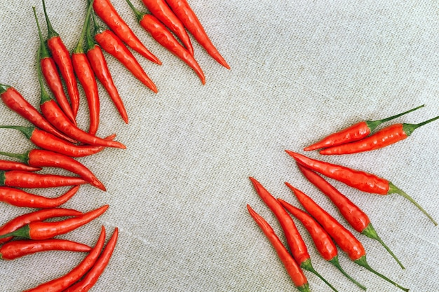 Small hot chili peppers on sackcloth. top view, flat lay. food background with red peppers and free space in the middle of the frame
