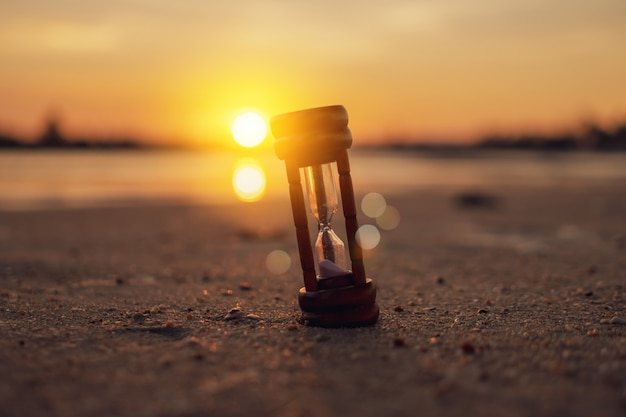 Small hourglass on a sandy beach