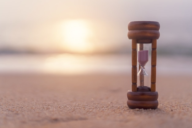 Small hourglass show time is flowing on sand beach background.
