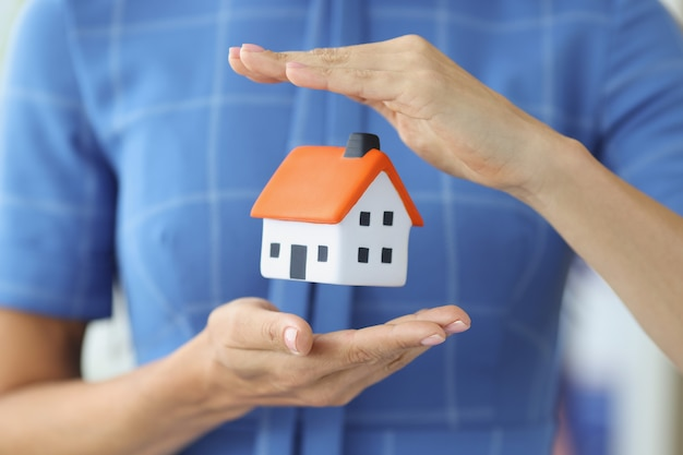 Small house in female hands of air home insurance concept