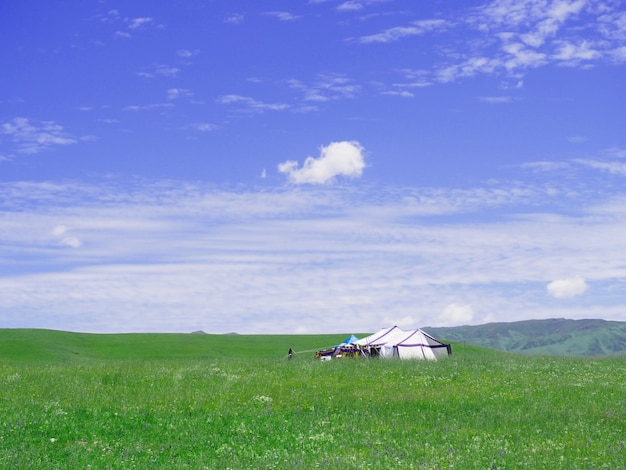 Small house in the grass field in the valley and the blue sky.