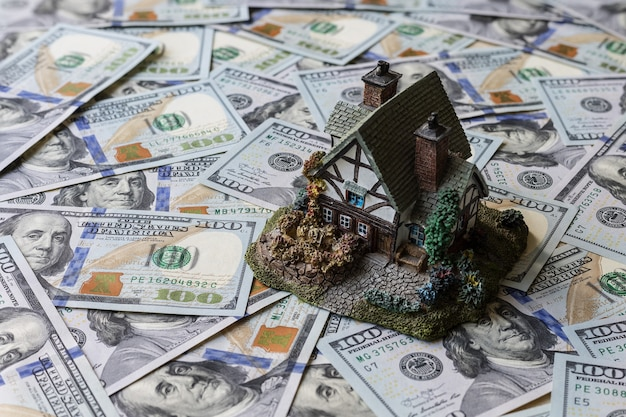A small house on hundred dollars banknotes background.. real estate loan concept.