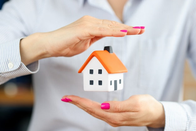 Small house inside female hands home insurance against natural disasters