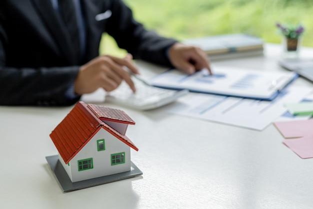 机の上に置かれた小さな家のモデル、ビジネスマンは販売マネージャーとの会議に出席して販売やプロモーションを行い、マーケティング計画はより多くの売上を生み出します。販売管理の概念。
