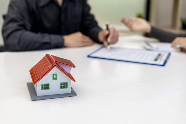 Модель небольшого дома размещена на столе, деловые люди посещают встречи с менеджерами по продажам для размещения продаж и рекламных акций, маркетинговые планы для увеличения продаж. концепция управления продажами.