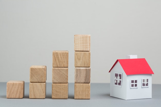 Modello di casa piccola e pila di crescente blocco di legno su sfondo grigio