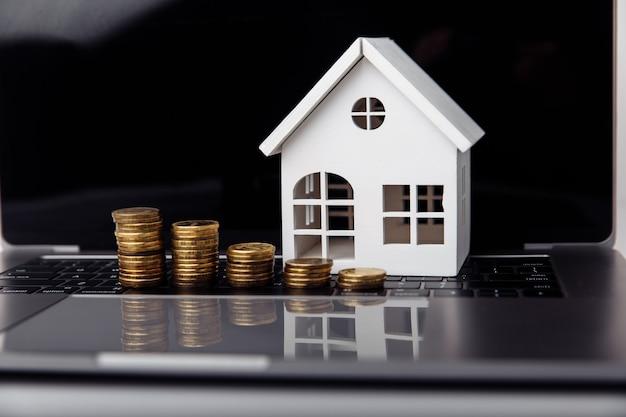 ノートパソコンとコインのクローズアップ住宅ローンの概念上の小さな家