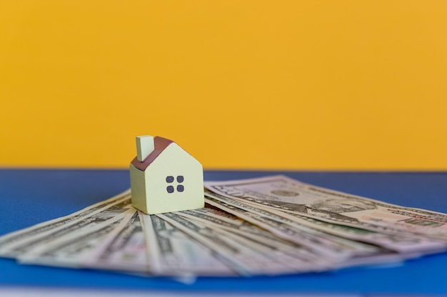 A small house stands on a bundle of dollars