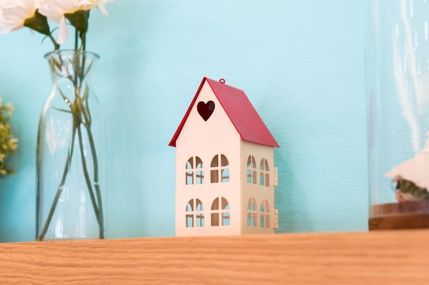Small house toy with heart shape on wooden shelf decoration