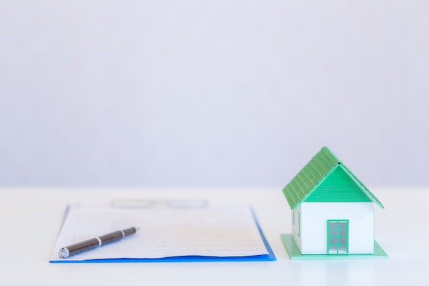 Домики современного дизайна и документы с ручкой на белом