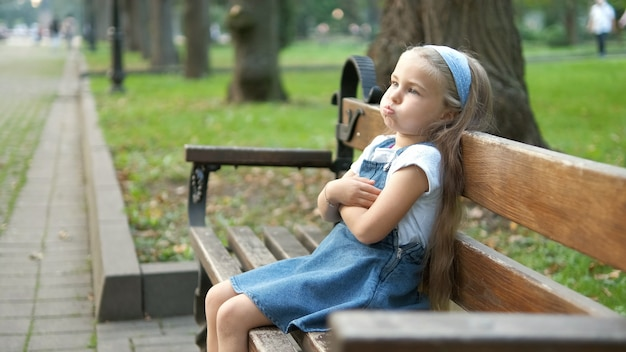 Small irritated child girl sitting alone on a bench in summer park.