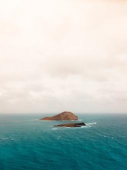 흐린 하늘 아래 바다에 작은 섬