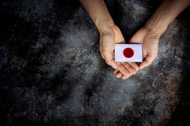 Малый флаг японии в руке. любовь, забота, защита и безопасная концепция.