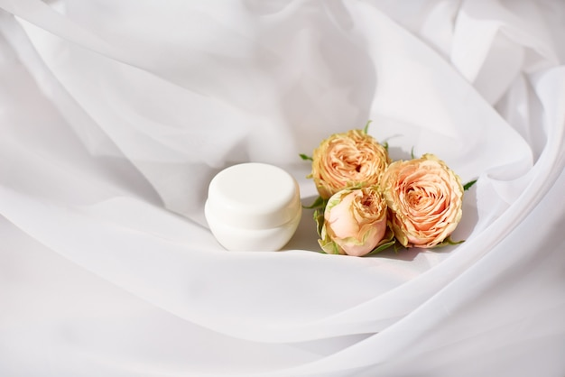 Small jar of expensive anti-aging or anti-wrinkle face cream with delicate roses on white cloth