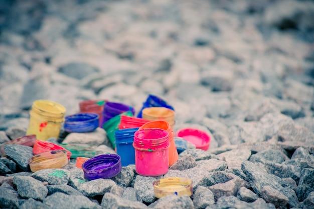 灰色の小石にさまざまな色のペンキの下から小さな瓶