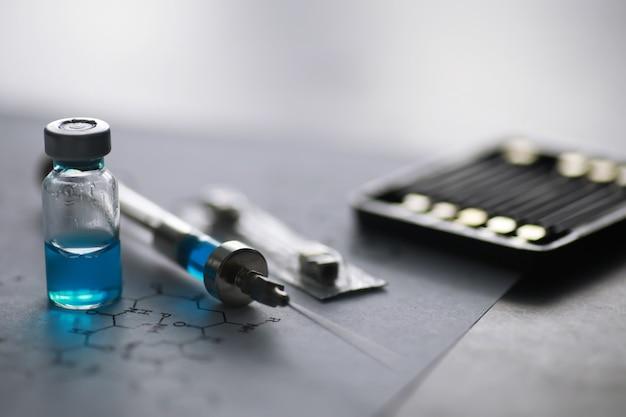 化学式の近くの青い背景に注射用注射器と注射器を備えた小さな瓶
