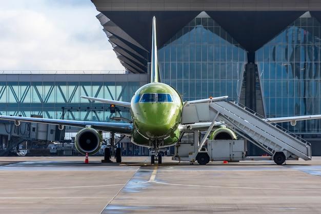 ターミナルビルの空港にランプが停まっている小型ジェット旅客機