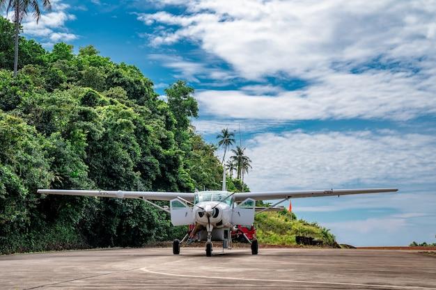 Парковка небольшого реактивного самолета на маленьком острове таиланда с горой позади.