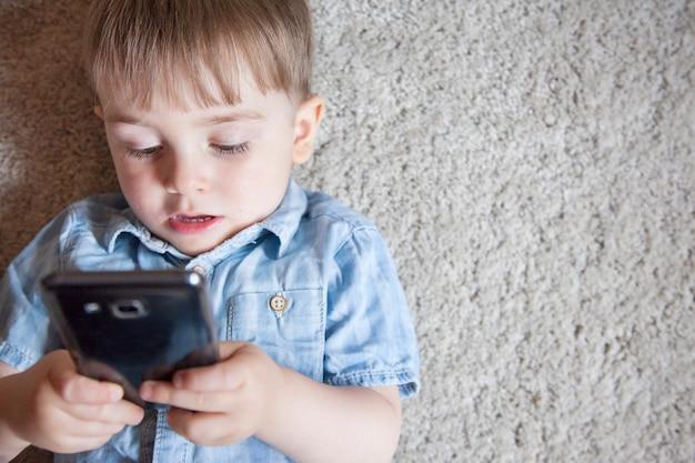 携帯電話でゲームをすることに夢中になっている小さな子供。子供の電子機器のペアレンタルコントロール。