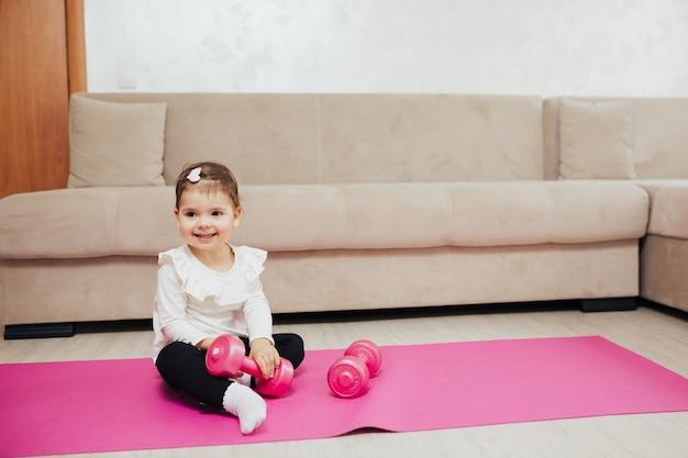 핑크 요가 매트에 아령으로 운동을하는 작은 아이