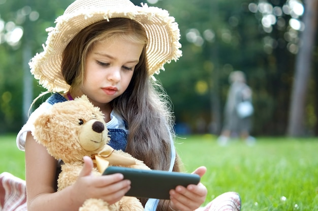 Small kid girl looking in her mobile phone together with her favorite teddy bear toy outdoors in summer park.