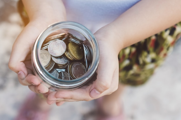 Small kid hands holding coins