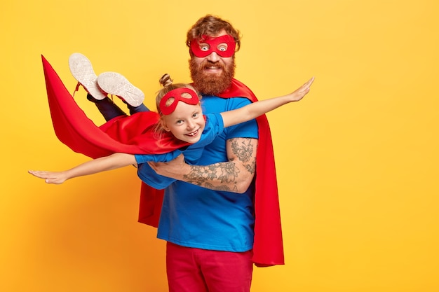 Small kid plays superhero, being on fathers hands, pretends flying