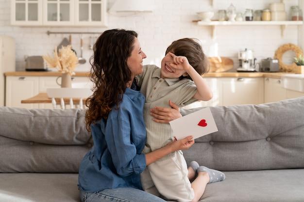 小さな子供は母の日の誕生日バレンタインの休日を抱きしめる心でお母さんのグリーティングカードを提示します