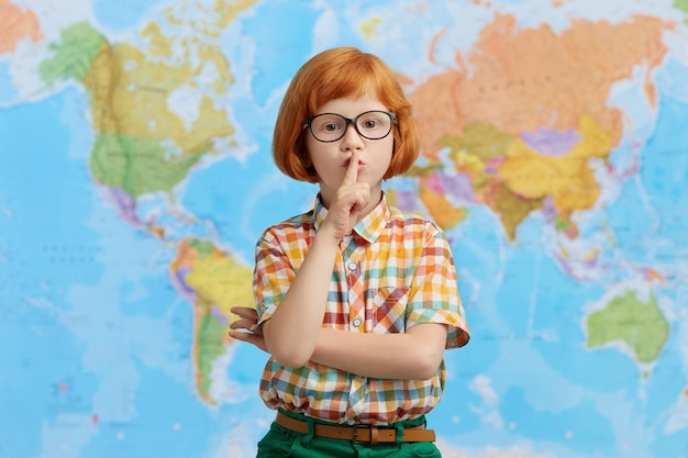 Small kid with ginger hair, wearing colorful checkered shirt and big eyewear, showing silence sign while standing in class room, asking pupils to be silent while teacher is away. education concept