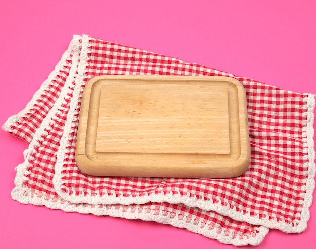 Small kitchen wooden cutting board and white red checkered kitchen towel