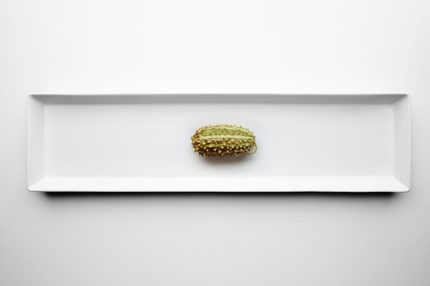 Small kivano pumpkin isolated in center of white plate