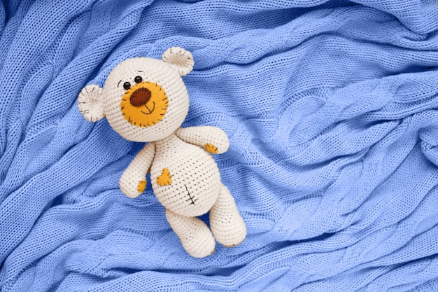 A small knitted amigurumi baby toy-bear is on a blue blanket