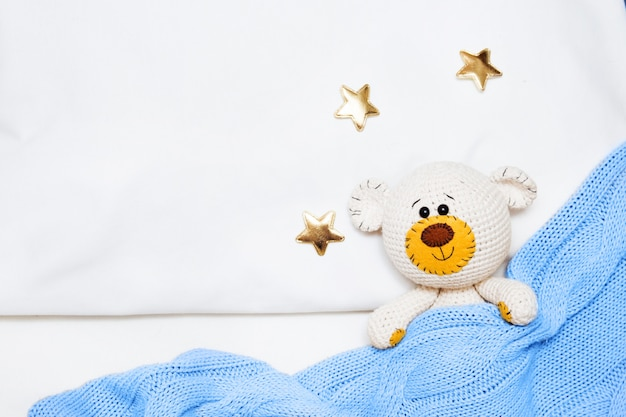 A small knitted amigurumi baby toy-bear is covered with a blue blanket