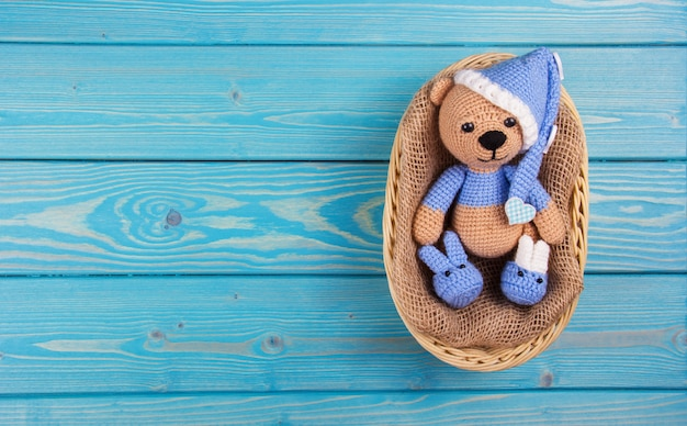 Small knitted bear lying in basket on blue wooden background