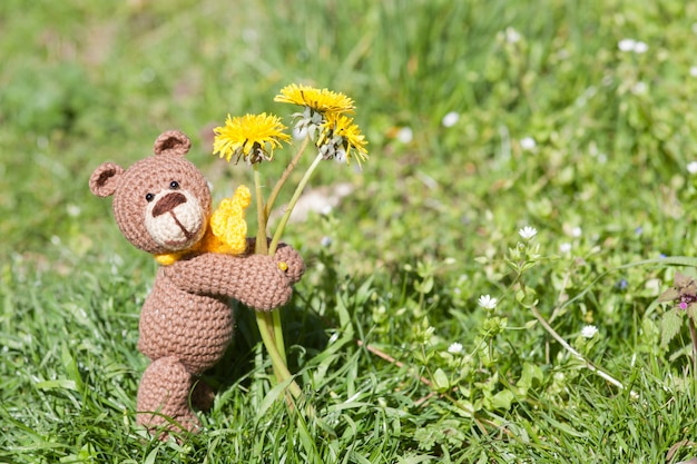 A small knitted brown bear with a yellow scarf in summer garden. knitted toy, handmade, amigurumi