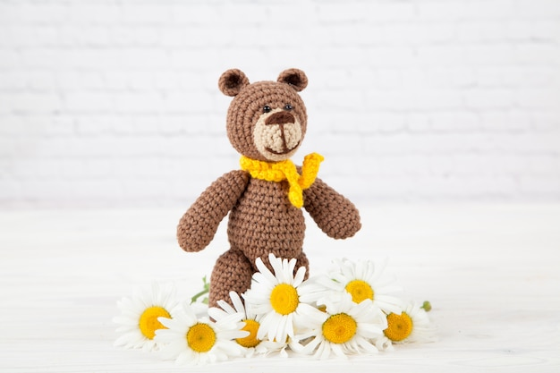 A small knitted brown bear with a yellow scarf with chamomile in white background.