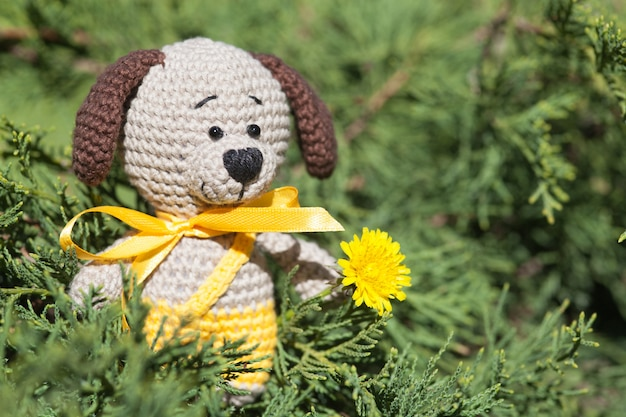 A small knitted brown dog with a yellow ribbon in summer garden. knitted toy, handmade, amigurumi