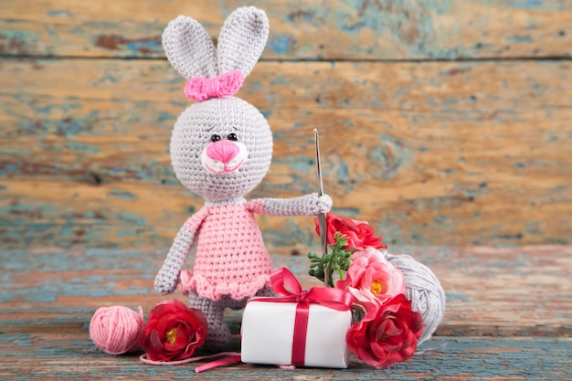 A small knitted gray rabbit in a pink dress on an old wooden background. knitted toy, handmade, needlework.