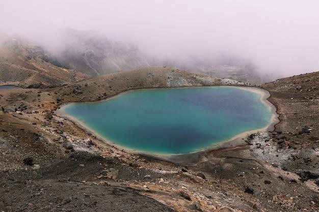 Piccolo lago nel mezzo del deserto vicino a una montagna in una giornata nebbiosa