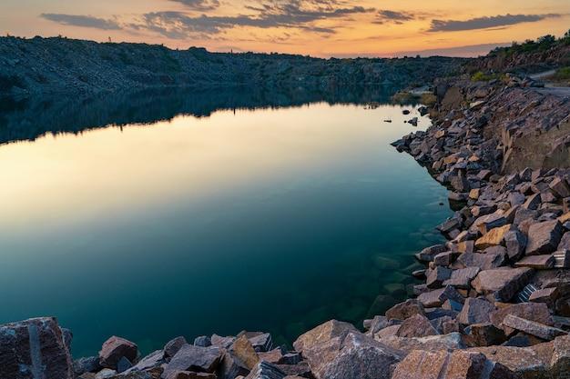 광산 작업에서 나온 돌 폐기물로 둘러싸인 작은 호수