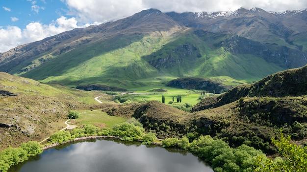 뉴질랜드에서 만든 무성한 녹색 언덕 풍경 샷이 있는 작은 호수