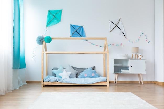 흰색 벽에 diy 연이 있는 소년 침실의 파란색 침구에 별 모양의 베개가 있는 침대 옆 찬장에 있는 작은 램프