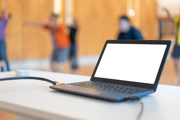 Small laptop on the table in front of exercise workout class with white solid clear screen.