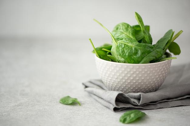 Маленькие листья свежего шпината в серой миске на белом столе