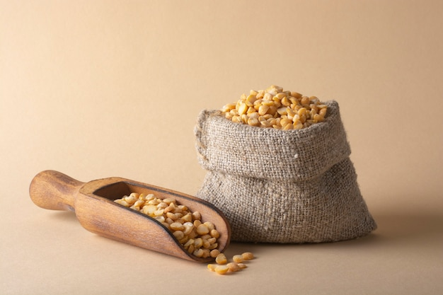 A small linen bag with peas and a wooden scoop. healthy food concept.