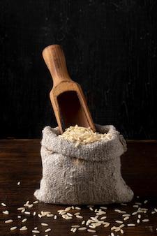 쌀과 오래 된 시골 풍 테이블에 나무 국자와 작은 리넨 가방. 프리미엄 사진