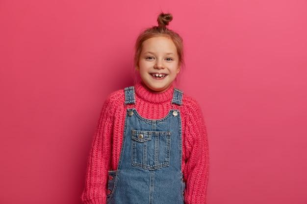이빨 미소를 짓는 작은 어린 아이, 니트 스웨터와 데님 사라 판을 입은 머리 롤빵은 기뻐 보이고 분홍색 벽 위에 포즈를 취하고 아이들과 놀러갑니다. 감정, 아이들