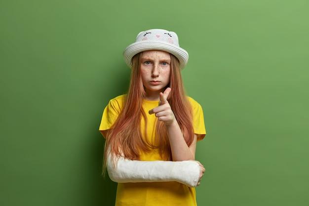 주근깨가있는 피부와 긴 생강 머리를 가진 작은 소녀는 당신을 가리키고 심각하게 보이며 모자와 노란색 티셔츠를 입고 우발적 인 가을 후 팔이 부러져 녹색 벽에 고립되었습니다.