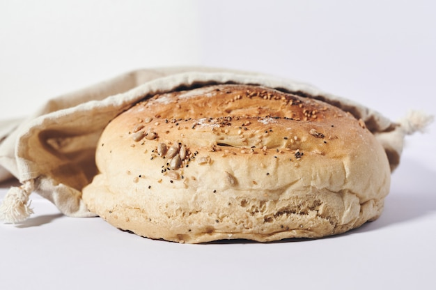 Small loaf of homemade bread in a cloth bag on a white background